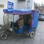 Ein schlafender Chinese in seinem Tuk-Tuk