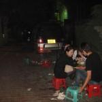 Auf der Straße in Mini-Plastikstühlen essende Chinesen